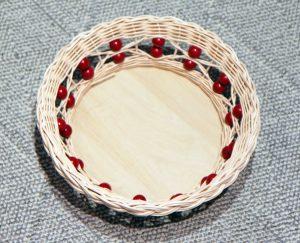 Pyöreä rottinkikori, jossa punaiset helmikoristeet kiertävät reunaa