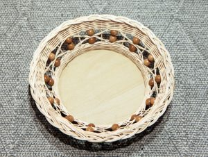 Pyöreä rottinkikori, jossa puunväriset helmikoristeet kiertävät reunaa