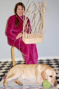 Kaisa punoo rottinkikoria ja opaskoira Sepi makaa hänen jalkojensa juuressa