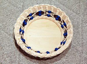 Pyöreä rottinkikori, jossa siniset helmikoristeet kiertävät reunaa